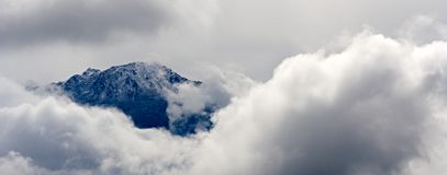 Black mountain and clouds. A black mountain surrounded by white clouds Royalty Free Stock Photography