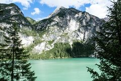 Black Mountain Near Green Body of Water Under Blue Sky Royalty Free Stock Image