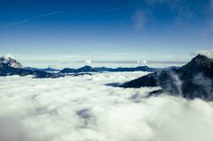 Black Mountain over White Clouds Stock Images