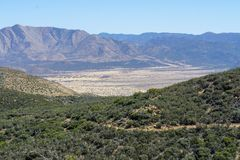Desert panorama with a nice view into a wide valley with small hills dead trees in the foreground royalty free stock images
