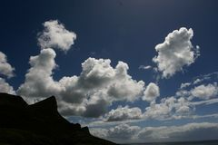 A silhouetted mountain with puffy clouds overhead. A black mountain with white, puffy clouds in the blue sky on a Summer`s day Royalty Free Stock Image