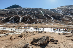 Black mountain witn snow and below with tourists on the ground with brown grass, snow and frozen pond in winter at Zero Point. Black mountain witn snow and Stock Image