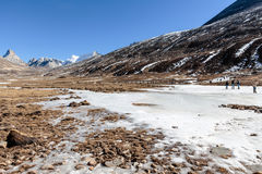 Black mountain witn snow and below with tourists on the ground with brown grass, snow and frozen pond in winter at Zero Point. Black mountain witn snow and Royalty Free Stock Photos