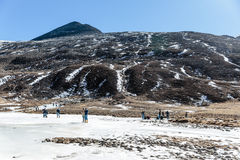 Black mountain witn snow and below with tourists on the ground with brown grass, snow and frozen pond in winter at Zero Point. Royalty Free Stock Image