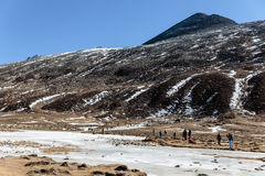 Black mountain witn snow and below with tourists on the ground with brown grass, snow and frozen pond in winter at Zero Point. Stock Images