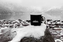 Cup for the inscription. black mug on the background of a mountain lake in winter royalty free stock photography