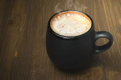 Black mug of coffee with froth and space for text Royalty Free Stock Image