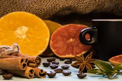A black mug of coffee next to cinnamon with puddings and chopped oranges royalty free stock image
