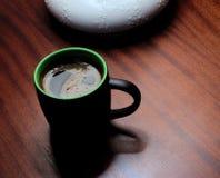 Black mug of coffee on table under lamp Royalty Free Stock Photo