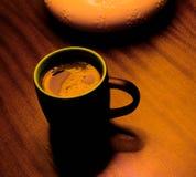 Black mug of coffee on table under lamp, golden Stock Image