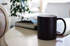 Black mug, cup on a table, Mockup