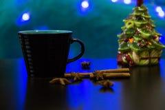 Black Mug with Hot Drink. Black Mug on a table with Christmas ornaments Royalty Free Stock Photography