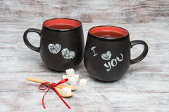 Black mug with inscription chalk I love you , wooden spoons Stock Image