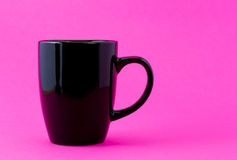 Black mug on pink Stock Images