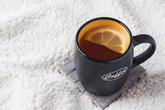 Black mug with tea and lemon on a warm soft blanket. Copy space top view.  stock images