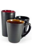 Black Mugs. Three black mugs isolated on white background Stock Images