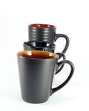 Black Mugs. Three black mugs isolated on white background Royalty Free Stock Images
