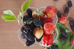 Black mulberry s red strawberries on wood background Royalty Free Stock Image
