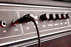 Black musical guitar amplifier panel with jack. Black guitar apmlifier panel with jack and cable Royalty Free Stock Image