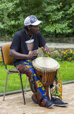 : Black musician from Africa demostrates how to play the drums Stock Photo