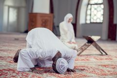 Black Muslim man and woman praying in mosque Stock Photos