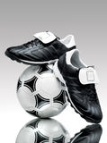 Black'n'wnite. A pair of cool football boots standing on a ball on a reflective surface Royalty Free Stock Photo