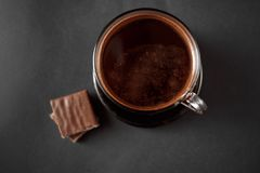 Black, natural, fragrant coffee in the transparent cup on a black background stock photography