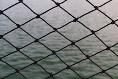 Black net and the lake water. Background Stock Photography