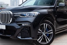 Black new BMW X7 xDrive40i 2019 year front led headlight, turned wheel and bumper view with light gray interior on parking in the