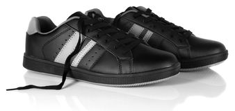 Black new sneakers with unfastened shoe laces Royalty Free Stock Images