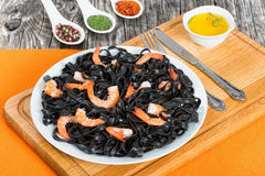 Black noodles with king prawns on white dish Stock Images