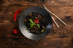 Black noodles with marbled beef on a wooden background stock image