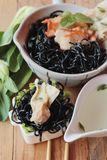 black noodles with pork and dumpling delicious Stock Image