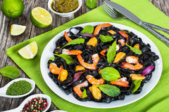 Black noodles salad with prawns, mussels, fresh green leaves Royalty Free Stock Photography
