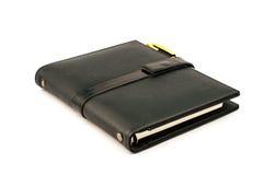 Black note book with ballpoint pen Stock Photos
