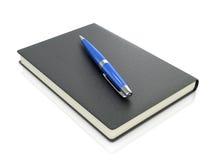 Black notebook with blue pen Stock Photos