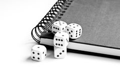 Black notebook with dices on white. Black notebook on spiral with dices  on white background Royalty Free Stock Images