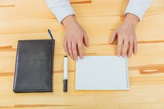 Black notebook with black marker on the table top view. At the office desk is a black notebook. Women`s hands on a notebook royalty free stock images