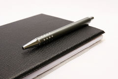 Black notebook with pen. On white Stock Images