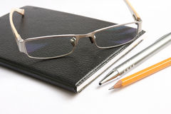 Black notebook pen pencil and glasses. The Black notebook pen pencil and glasses Royalty Free Stock Photos