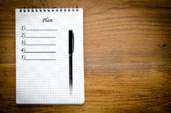 Black notebook with pen on a wood background Stock Images