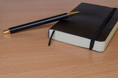 Black notebook with a pen Royalty Free Stock Photos
