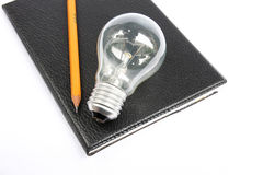 Black notebook with pencil and light bulb. The Black notebook with pencil and light bulb Royalty Free Stock Photos