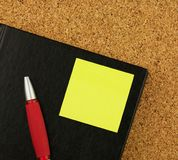 Black notebook, red pen and yellow sticker on the cork board background. Royalty Free Stock Photos