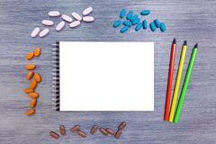 Notepad with pencils and pills. Black notebook with three pencils lie on the table. Notepad with pencils stock photo