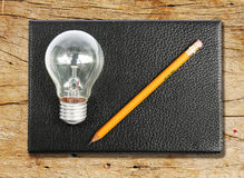 Black notebook with yellow pen cil and light bulb. The Black notebook with yellow pen cil and light bulb on wood Stock Photos
