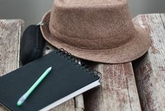Black notepad, green pan, glasses case and hat on bench in park close up royalty free stock image