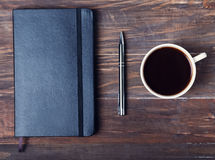 Black notepad, pen and cup of black coffee on the wooden table Royalty Free Stock Photography