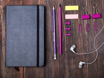 Black notepad and pink color stationery on the wooden table Royalty Free Stock Image