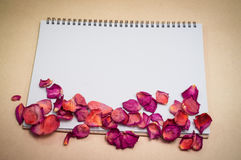 Black notepad. Realistic template notebook. Blank cover design. With dried rose petals and leaf. on cardboard background stock photo